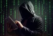Computer hacker with digital tablet stealing data concept for network security, cyber attack or ransomware poster