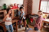 Three young adult girlfriends talk in kitchen, elevated view poster