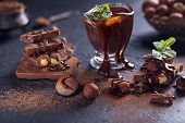 Homemade hazelnut spread or hot chocolate in glass bowl with nuts and chocolate bar. Cocoa powder nuts and chocolate background. Ingredients for cooking homemade chocolate sweets. Sweets concept. poster