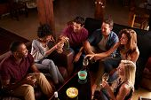 Young adults socialising at a party at home, elevated view poster