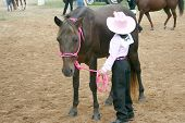 this young cowgirl is waiting her turn in the arena for the competition. poster