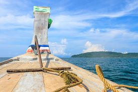 head of wooden boat toward the tropical sea in sunny day