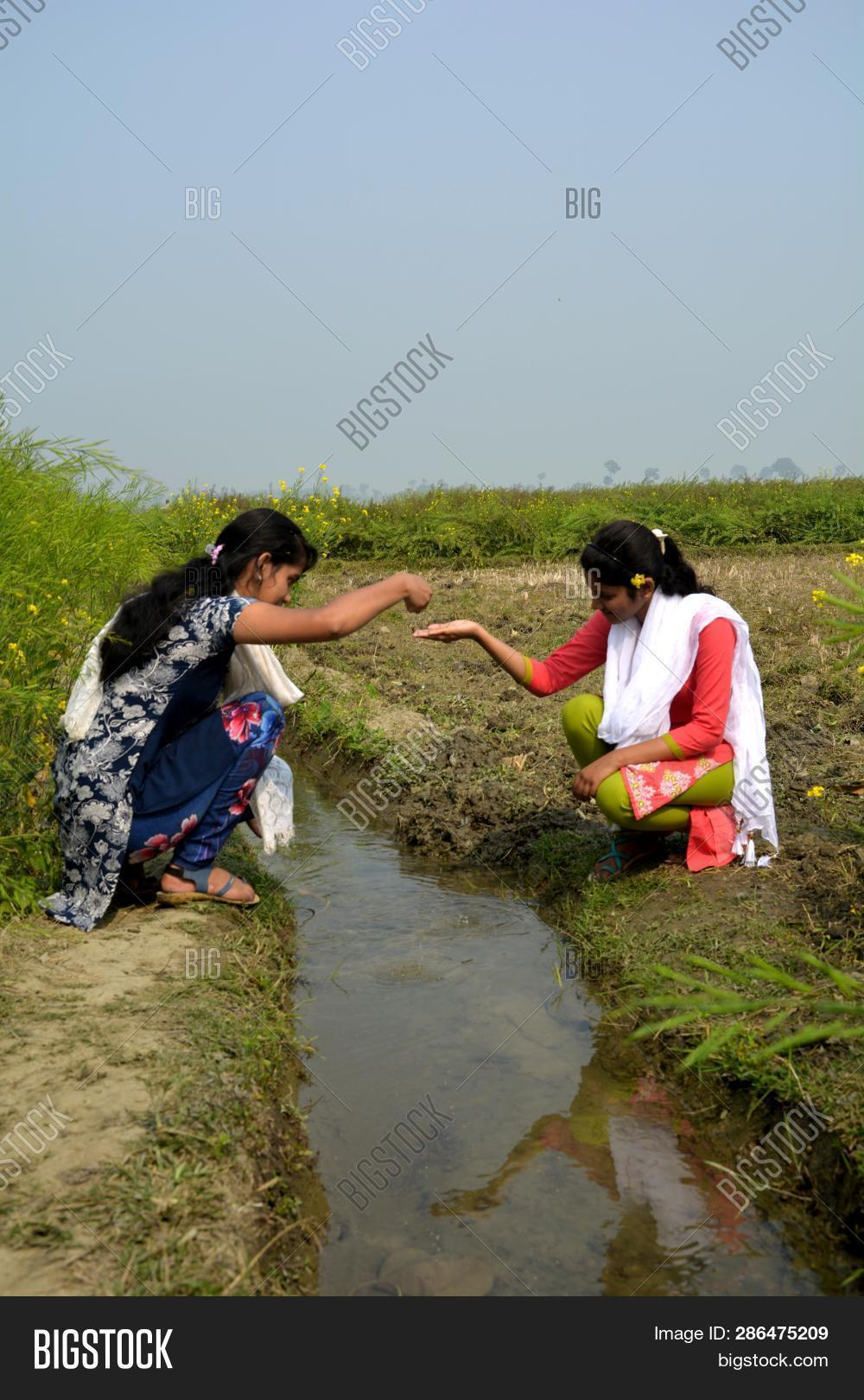 68a5b20676 Close Up Of Two Young Girls Sitting Outside In A Field On A Water Canal  Taking