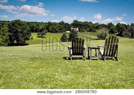 Two Adirondack Chairs With A Glass Of Wine Over Looking A Green Rolling Pasture.