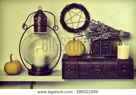 Old-fashioned lamp with lavender bunch, small pumpkins and old box. Magic gothic ritual. Wicca, esoteric, divination and occult background with vintage objects poster