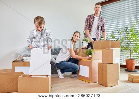 Boy and parents of a family on the move pack together moving boxes