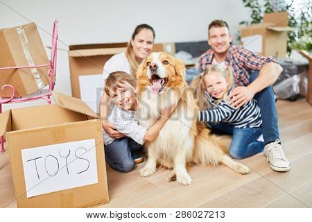 Happy family with dog after moving in new house as a home