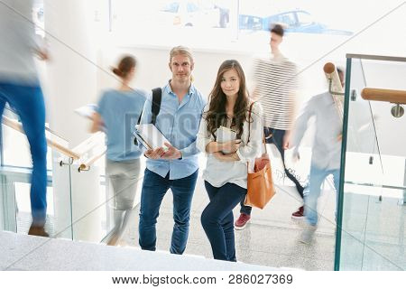 Young couple as freshmen in uni at busy staircase