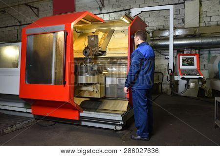 The Worker In Blue Workwear, The Operator Of The Cnc Machine, Oversees The Process And Controls It.