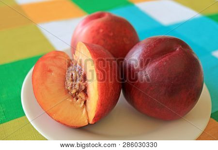 Two Fresh Ripe Nectarine Whole Fruits With One Cut Nectarine On A White Plate Served On Vibrant Colo