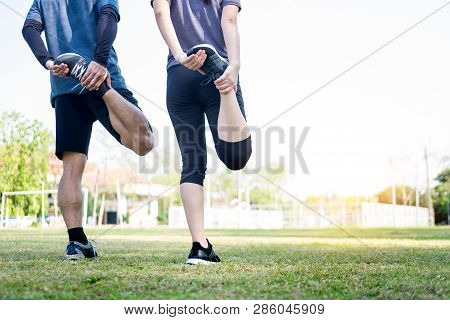 Early Morning Workout, Fitness Couple Stretching Outdoors In Park. Young Man And Woman Exercising To