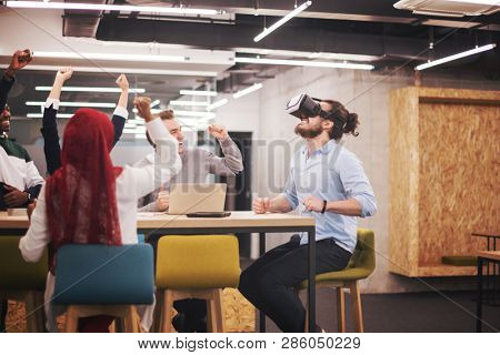 Multiethnic Business team using virtual reality headset in office meeting  Developers meeting with virtual reality simulator around table in creative office.