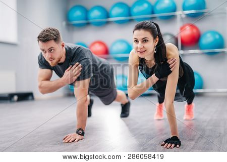 Beautiful Woman And Strong Male Doing Push-ups On One Hand With A Background Of Fitness Balls. Young