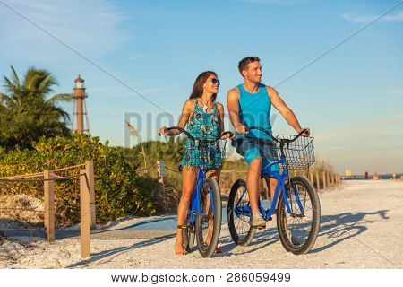 Florida beach vacation couple biking sport rental bikes recreational activity happy watching sunset on Sanibel Island by the Lighthouse. Young woman and man riding bicycles. Summer people lifestyle .