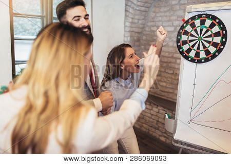 Business People Making Team Training Exercise During Team Building Seminar, Play Darts. Indoor Team