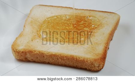 Toast On A Plate Pour With Honey. 4k Uhd 3840x2160 Video Clip
