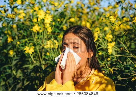 Sneezing Young Girl With Nose Wiper Among Blooming Flowers In Park. Young Woman Got Nose Allergy, Fl