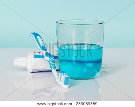 Toothbrush, Toothpaste, Mouthwash On A White-blue Background. The Concept Of Daily Dental Care, Oral