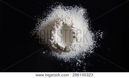 Easter Concept, Handrful Of Flour With Hole In The Center Shape Like Egg On Black Table. Preparation