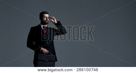 Businessman over dark background. World map background. Business, globalization, capitalism concept.