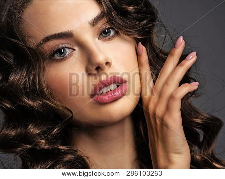Closeup face of a beautiful woman with a smoky eye makeup. Pretty  girl with a natural nails. Portrait of an attractive female posing at studio. Woman with a modern nails.