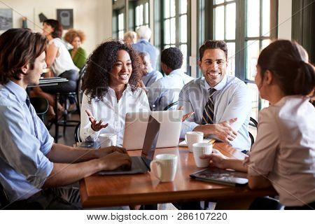 Business Team Having Informal Meeting Around Table In Coffee Shop
