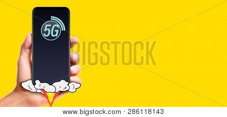 male hand hold launching 5G smartphone, on yellow background.