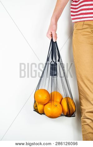 Holding A Reusable String Bag Full Of Oranges. Sustainable Eco Packaging Concept: Shopping For Groce