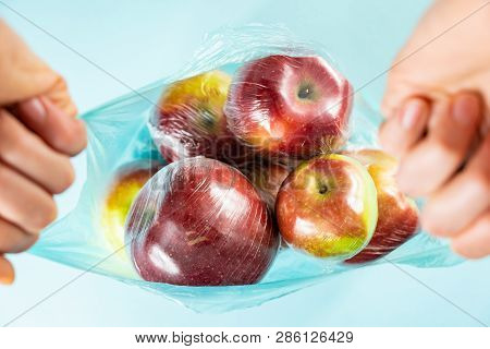 Excessive Plastic Use Concept: Fresh Apples In Kitchen Wrap In A Plastic Bag. Unreasonably Over-pack
