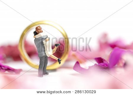 Couple Hug In The Pink Garden With A Wedding Ring