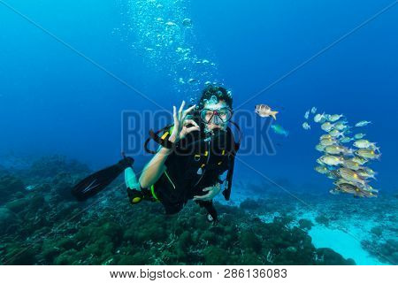 Young woman scuba diver showing OK gesture. Underwater sport and leasure activities.