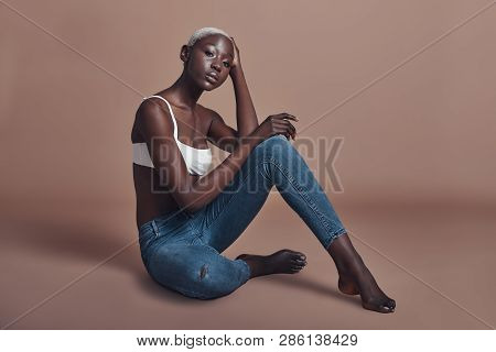 Gorgeous Sensual Model. Attractive Young African Woman Looking At Camera While Sitting Against Brown