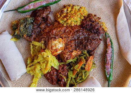 Injera served with Chicken and egg Doro Wat, berbere, vegetables and lentils.  Injera, the national dish of Ethiopia, is a sourdough flatbread made from teff flour. poster