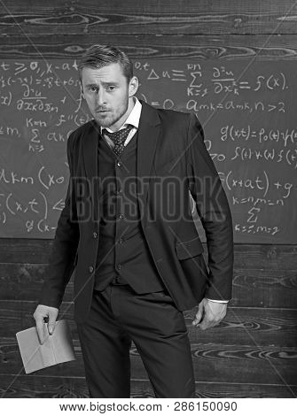 Frowning Guy Holding Open Book In His Hand. Anxious Young Professor Giving Explanations To Students.