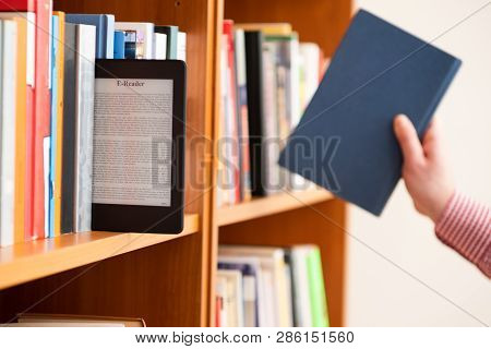 Hands Holding And Keeping Ebook On Bookshelf Background