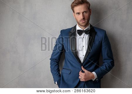 Ellegant man buttoning his jacket with a hand in his pocket on a light grey background