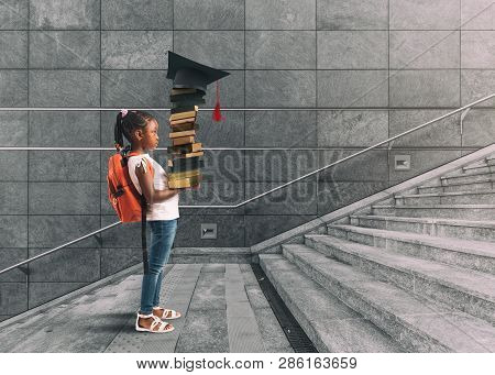 Little Girl With Backpack On Her Shoulder, And Books In Hand, Who Undertakes A Training Course Think