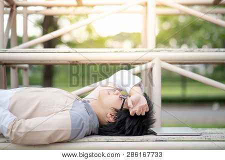 Asian Man University Student With Glasses Lying Down On Cheer Stand Near His Laptop Computer. Relaxi