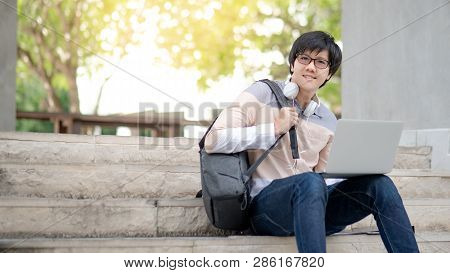 Young Asian Man University Student With Glasses And Headphones Sitting On The Stair Working With Lap