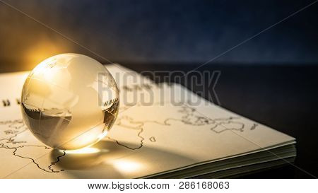 World Globe Crystal Glass On World Map Outline Sketch On Paper Page Of Notebook. Travel Around The W