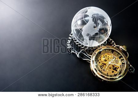 Global Business Concept. World Globe Crystal Glass And Silver Pocket Watch On Glossy Table. Time Man