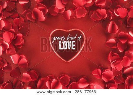 Top View Of Beautiful Heart With Groovy Kind Of Love Lettering And Decorative Petals On Red Backgrou