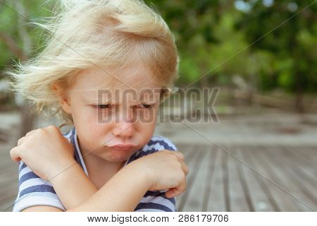 Face Portrait Of Annoyed And Unhappy Caucasian Kid With Crossed Arms. Upset And Angry Child Concept