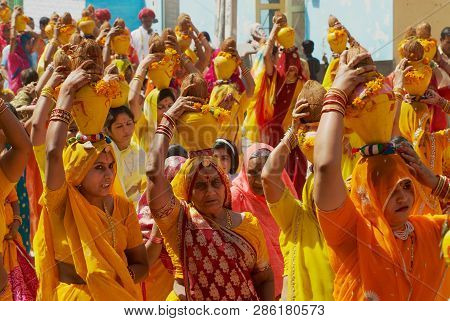 Bikaner, India, April 01, 2007: A Crowd Of Rajasthani Women Wearing Yellow And Red Sarees Holding Co