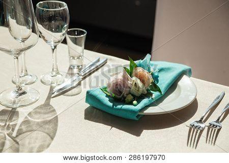 Aquamarine Serviette With Flower Decor Lying On The Dinner Plate