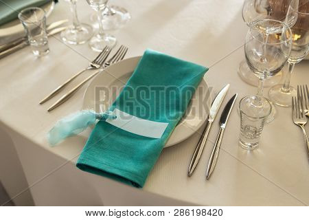 Guest Card And Aquamarine Serviette With Lying On The Dinner Plate