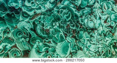 Malachite green mineral gemstone texture,malachite background, green background. Amazing polished natural slab of green malachite mineral gemstone specimen gemstone macro as a background