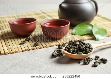 Composition With Spoon Of Tie Guan Yin Oolong Tea And Brewed Beverage On Grey Table