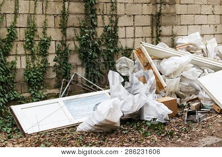 Construction Garbage After Apartment Repair. Pile Of Construction Waste Near A White Brick Wall. Con