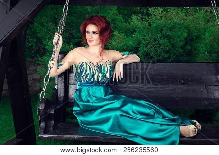 Portrait Of Beautiful Young Girl Woman In Long Green Dress Sitting In The Chair Enjoying Nature. Neu